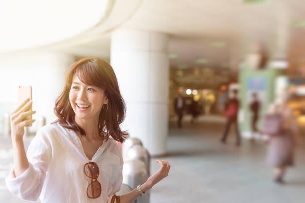ビデオチャットを作るモールで若い笑顔観光女性 - スマホ 女性 ストックフォトと画像