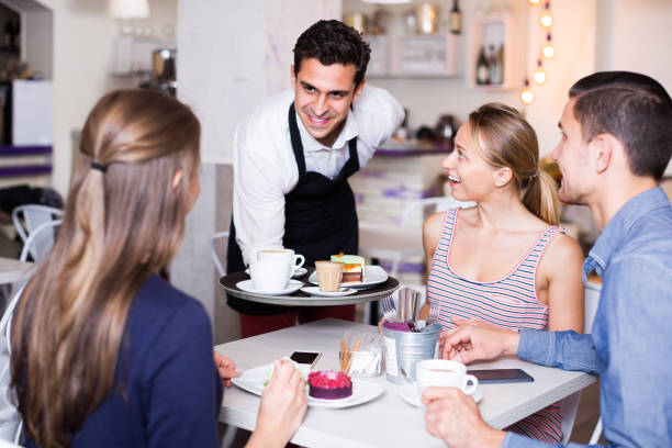 young smiling waiter bringing ordered dishes to friends in tearoom young smiling waiter bringing ordered dishes to friends in tearoom of a cozy confectioner's shop tea room stock pictures, royalty-free photos & images
