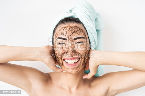 istock Young smiling woman applying coffee scrub mask on face - Happy girl having skin care spa day at home - Healthy alternative natural exfoliation treatment and people lifestyle concept 1226805198