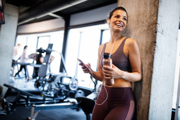 Young smiling woman at the gym relaxing and listening to music using a mobile phone stock photo