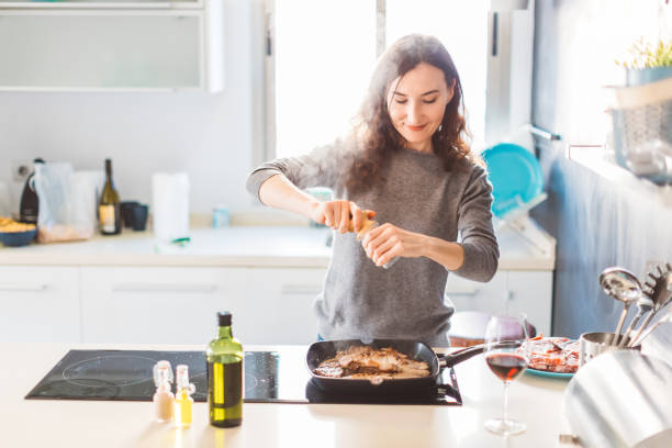 Young smiling woman cooking in the kitchen, adding pepper to the grilled meat. Healthy food concept.