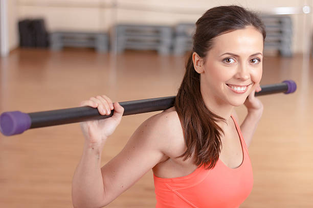 Young smiling woman doing stick exercises Various exercises. Portrait of smiling young woman doing stick exercises in gym. broom stock pictures, royalty-free photos & images