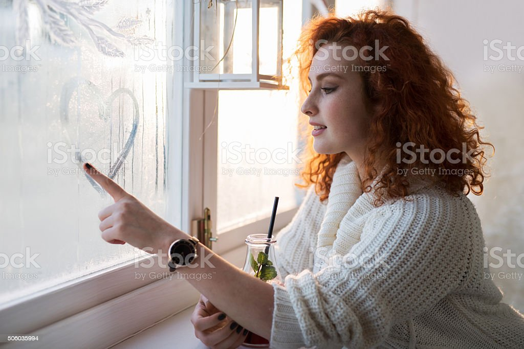 Young smiling woman drawing a heart on a window. stock photo