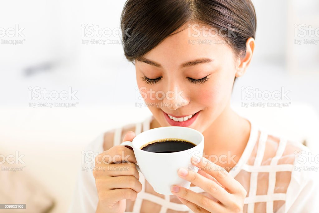 young smiling woman drinking coffee in the morning stock photo