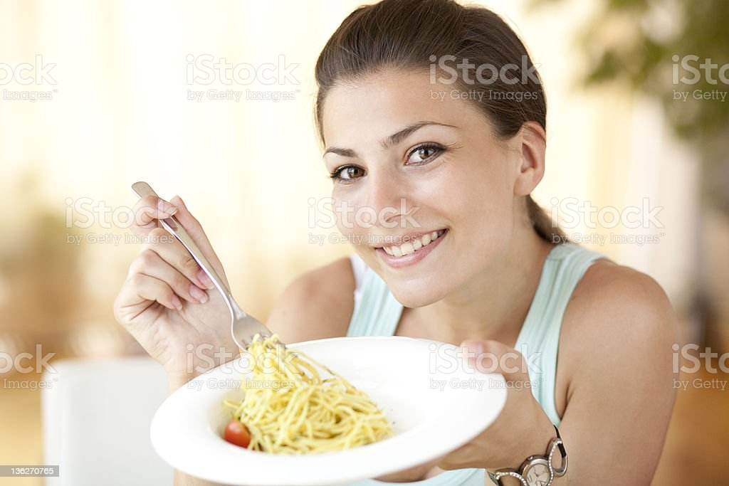 Young smiling woman eating pasta royalty-free stock photo