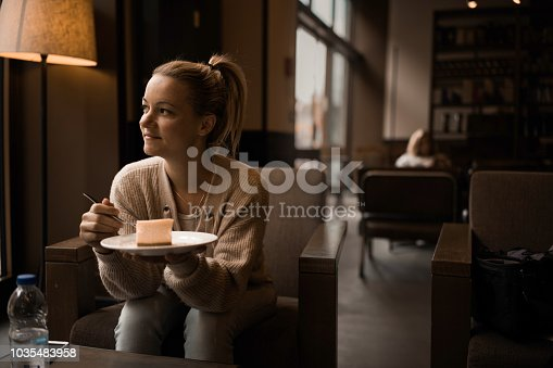 Smiling woman having a piece of cake and looking away while relaxing in a cafe.