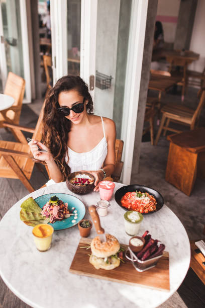 Young smiling woman having breakfast in stylish street cafe. Smoothie bowl, matcha latte, tacos and burger stock photo