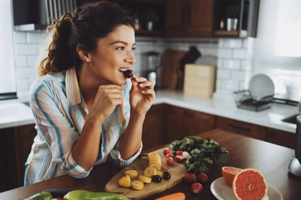 A young smiling woman having healthy breakfast in the morning stock photo