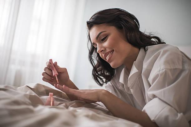 junge lächelnde frau mit maniküre-behandlung im schlafzimmer. - nägel lackieren stock-fotos und bilder