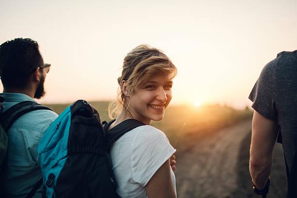 joven mujer sonriente excursionismo. - mochilero fotografías e imágenes de stock