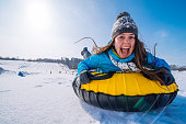 istock young smiling woman hold on for sleigh. snow tubing. winter activity 1080901398