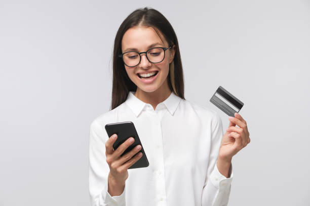 young smiling woman holding credit card and smartphone, isolated on gray background - paying with card imagens e fotografias de stock
