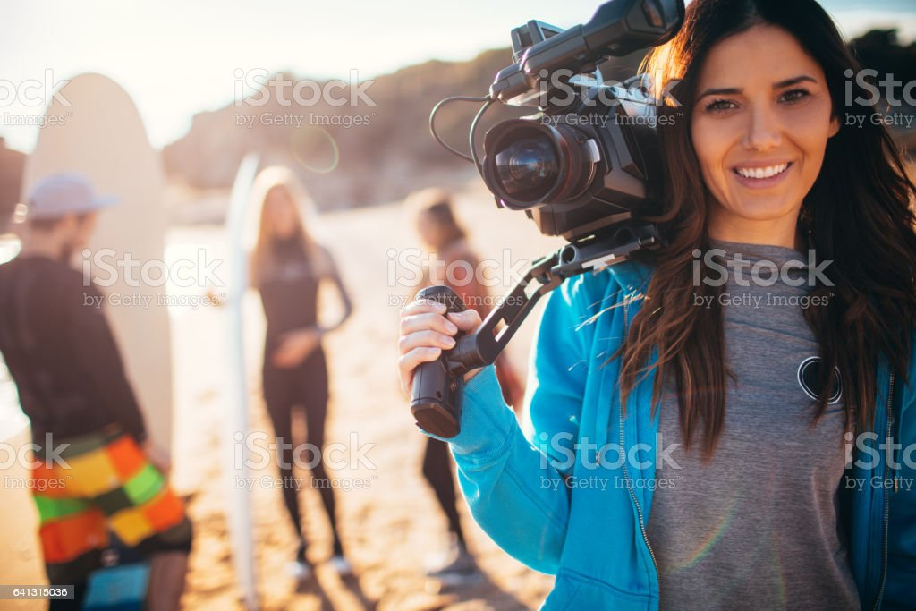 Young smiling woman holding video camera stock photo