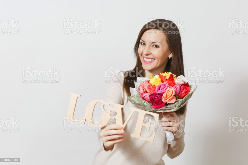 Young smiling woman holding wooden word Love, bouquet of beautiful roses flowers isolated on white background. Copy space for advertisement. St. Valentine's Day or International Women's Day concept. stock photo