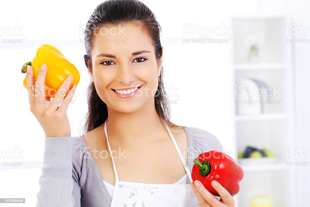 Young smiling woman holding yellow and red peppers. royalty-free stock photo