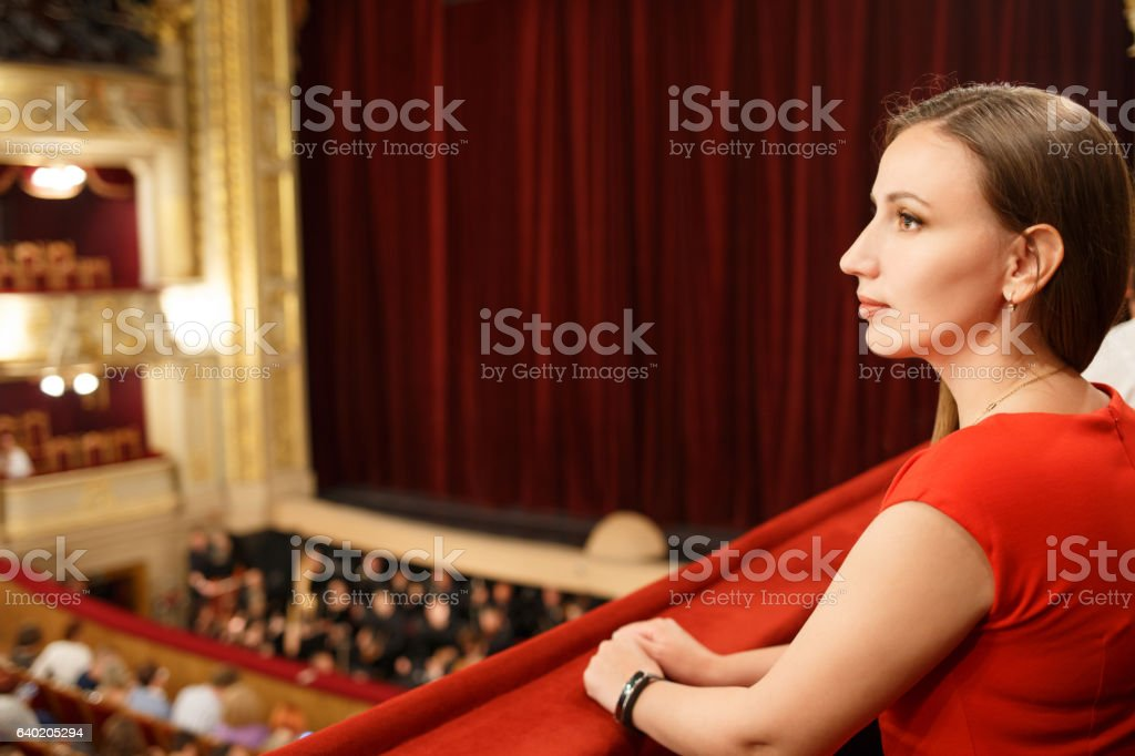 Young smiling woman in dress sitting in theatre ロイヤリティフリーストックフォト