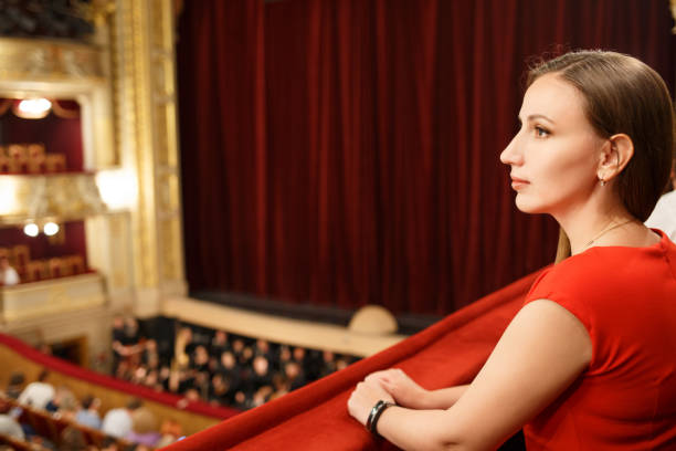 Young smiling woman in dress sitting in theatre - foto stock