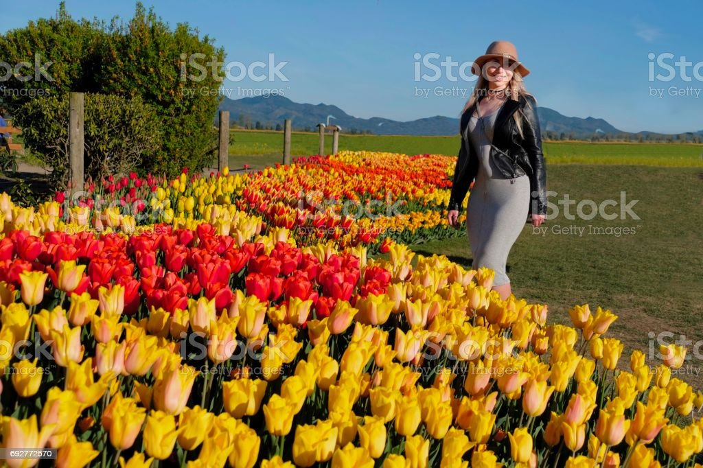 Young smiling woman in garden by tulip beds. stock photo