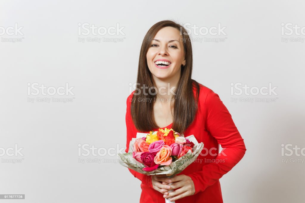 b1fe2030dda11 Young smiling woman in red clothes holding bouquet of beautiful roses flowers  isolated on white background. Copy space for advertisement.