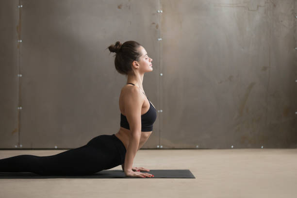 Young smiling woman in Urdhva mukha shvanasana pose, grey studio Portrait of young attractive yogi woman practicing yoga, doing Urdhva mukha shvanasana exercise, upward facing dog pose, working out wearing black sportswear, cool urban style grey studio, copy space namaskard geothermal area stock pictures, royalty-free photos & images