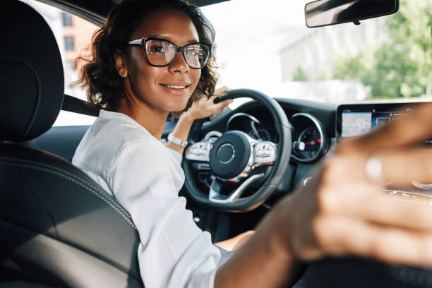 Young smiling woman looking at rear window and parking a car stock photo