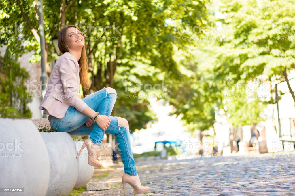 Young smiling woman outdoors waiting for someone royalty-free stock photo