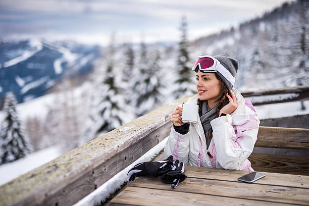 Young smiling woman relaxing in a cafe at ski resort. Smiling woman enjoying in a hot drink at ski cafe and day dreaming. ski resort stock pictures, royalty-free photos & images
