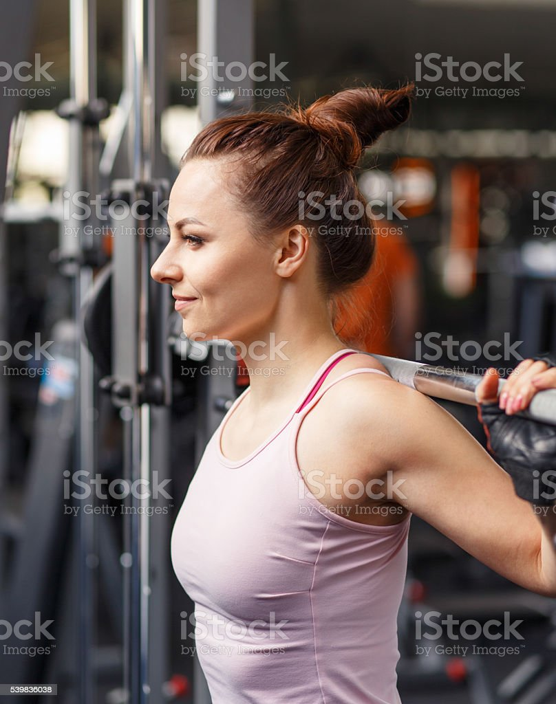 Young smiling woman squatting with barbell in gym stock photo