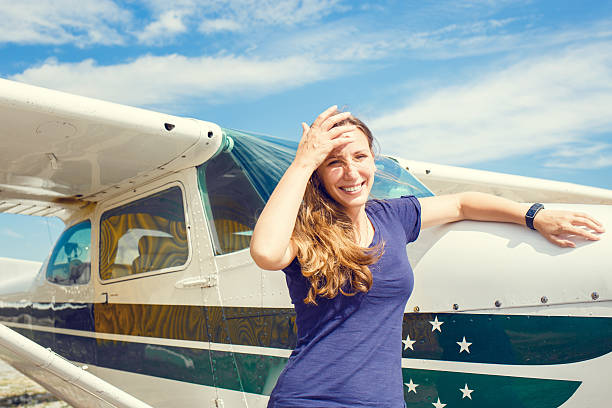 Young smiling woman standing near private plane Young smiling woman standing near private plane ready for flight sergionicr stock pictures, royalty-free photos & images
