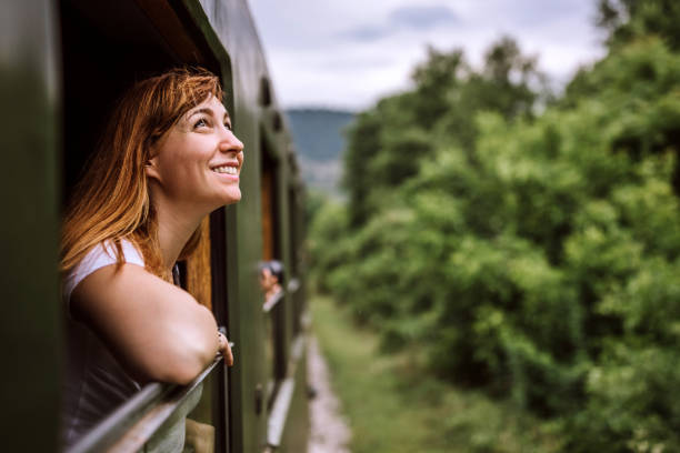 Young smiling woman standing out of the train window while travelling stock photo