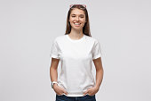 istock Young smiling woman standing with hands in pockets, wearing blank white t-shirt with copy space for your logo or text, isolated on gray background 1150254169