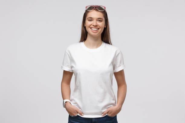 주머니에 손으로 서 있는 젊은 웃는 여자, 로고 또는 텍스트, 회색 배경에 고립에 대 한 복사 공간을 가진 빈 흰색 티셔츠를 입고 - 백인종 뉴스 사진 이미지
