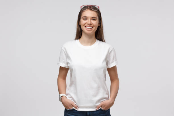 Young smiling woman standing with hands in pockets, wearing blank white t-shirt with copy space for your logo or text, isolated on gray background Young smiling woman standing with hands in pockets, wearing blank white t-shirt with copy space for your logo or text, isolated on gray background shirt stock pictures, royalty-free photos & images