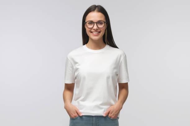 junge lächelnde frau steht mit händen in taschen, trägt leeres weißes tshirt mit kopierraum, isoliert auf grauem hintergrund - europäischer abstammung stock-fotos und bilder