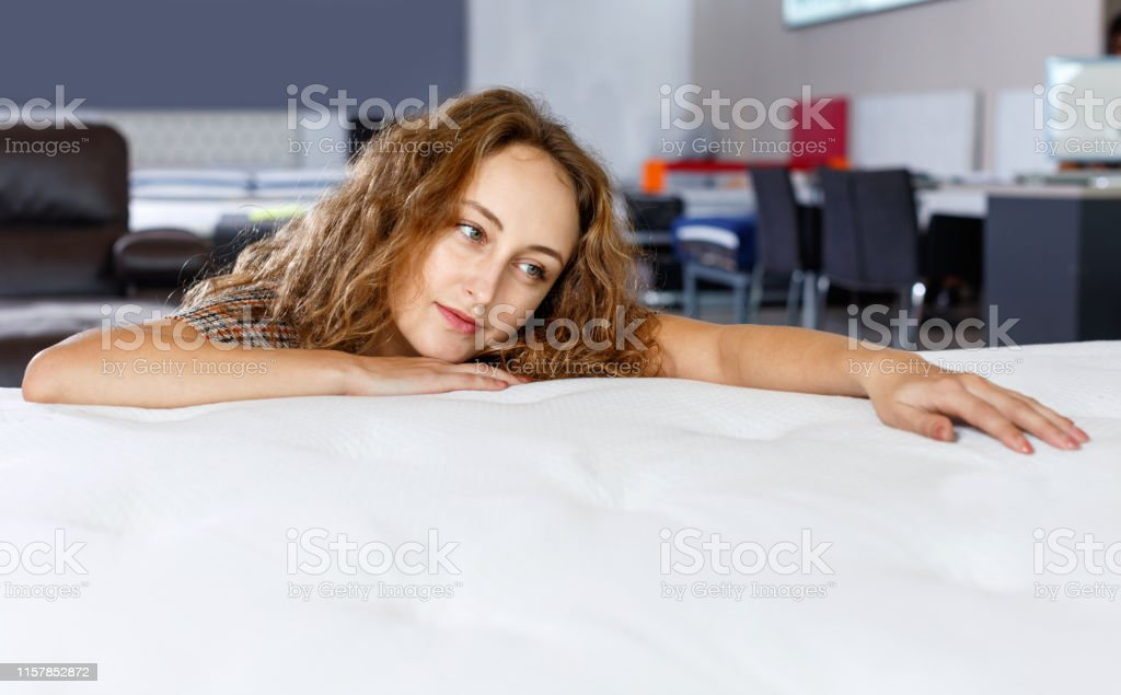 Young glad cheerful positive woman testing new mattress in modern...