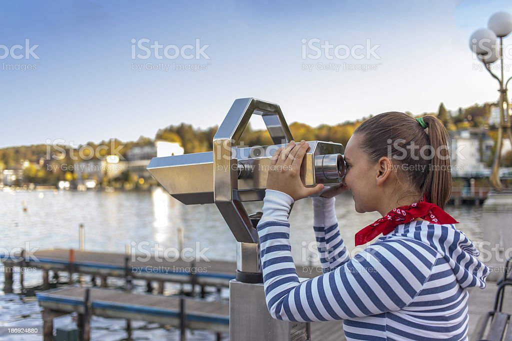 Young smiling woman using coin operated binoculars royalty-free stock photo