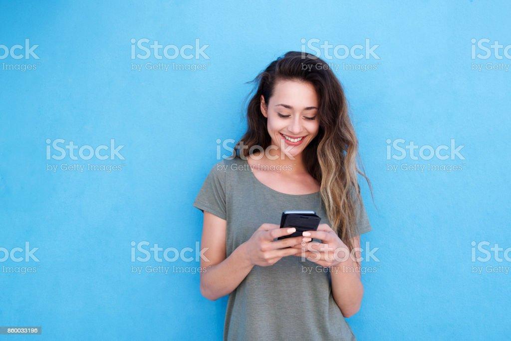 使用手機在藍色背景下的微笑少婦 - 免版稅20多歲圖庫照片