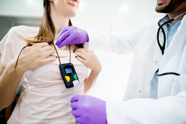 Young smiling woman wearing a holter heart monitor. stock photo