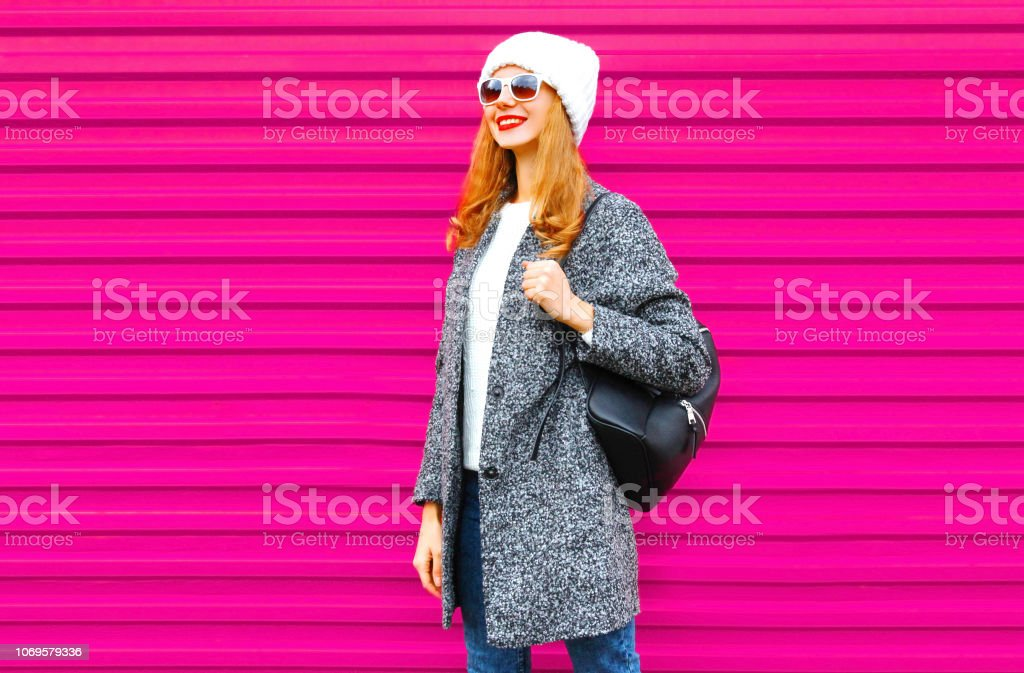 Young smiling woman wearing gray coat, hat, backpack walking in city on colorful pink wall background stock photo