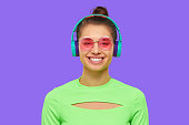 istock Young smiling woman wearing neon green top, pink round glasses and wireless headphones, enjoying listening to music, isolated on purple background 1227242535