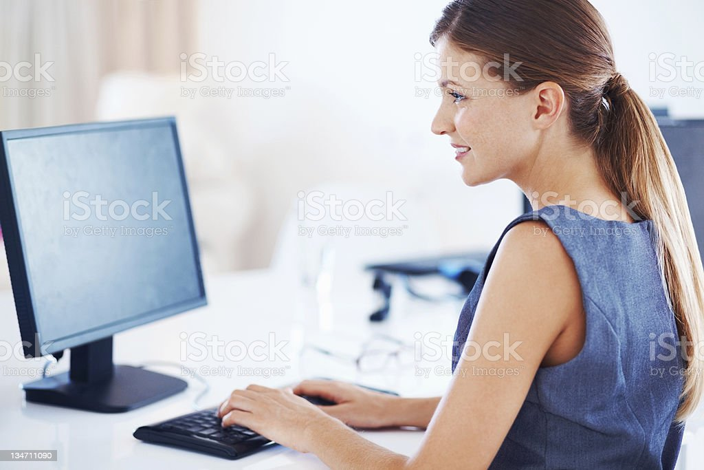 Young smiling woman with computer in an office royalty-free stock photo