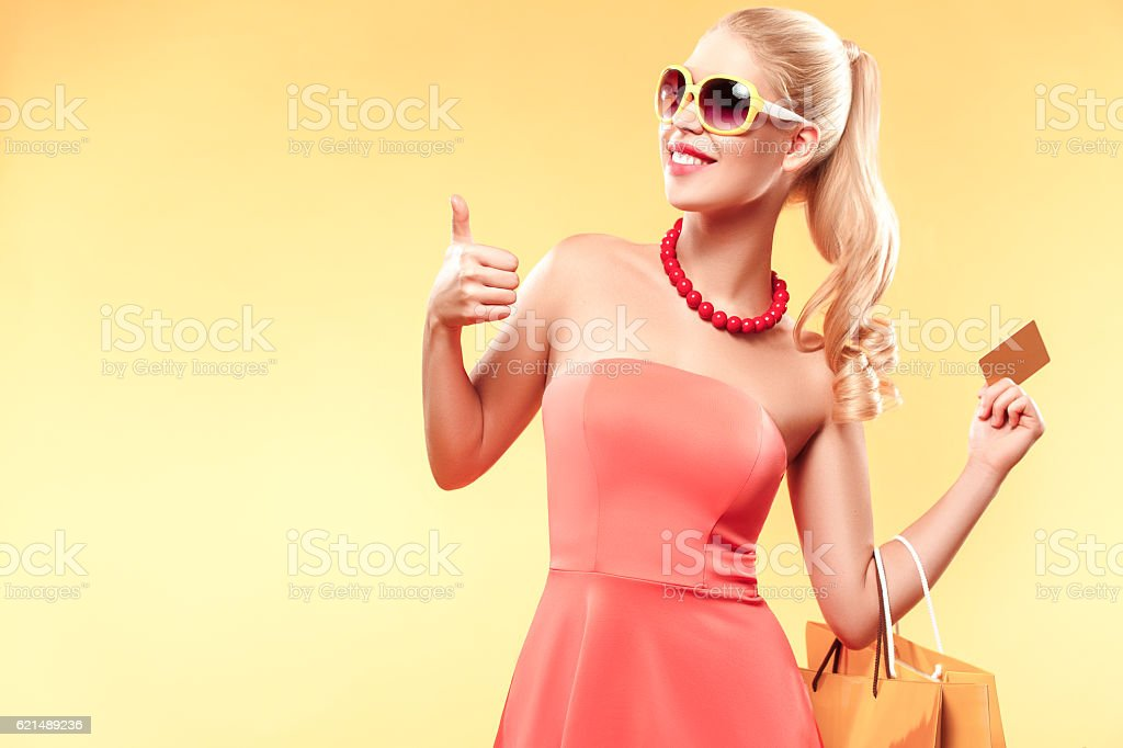 Young smiling woman with shopping bags make her thumb up photo libre de droits