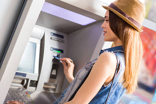 Young smiling woman withdrawing money from ATM. stock photo