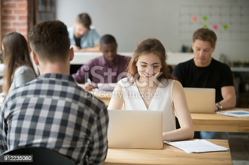 1031394390 istock photo Young smiling woman working on laptop in coworking office space 912235060