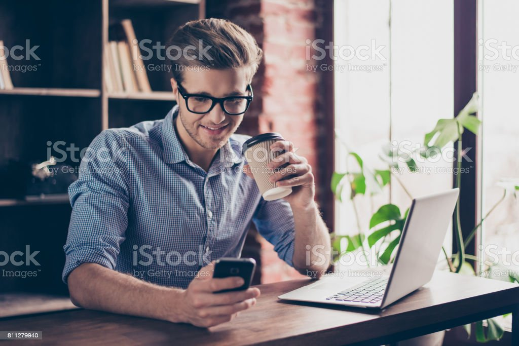 Young smiling worker drinking coffee and typing message royalty-free stock photo