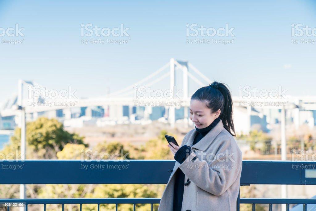 スマート フォンを使用して若い smilling アジアの女の子 ストックフォト