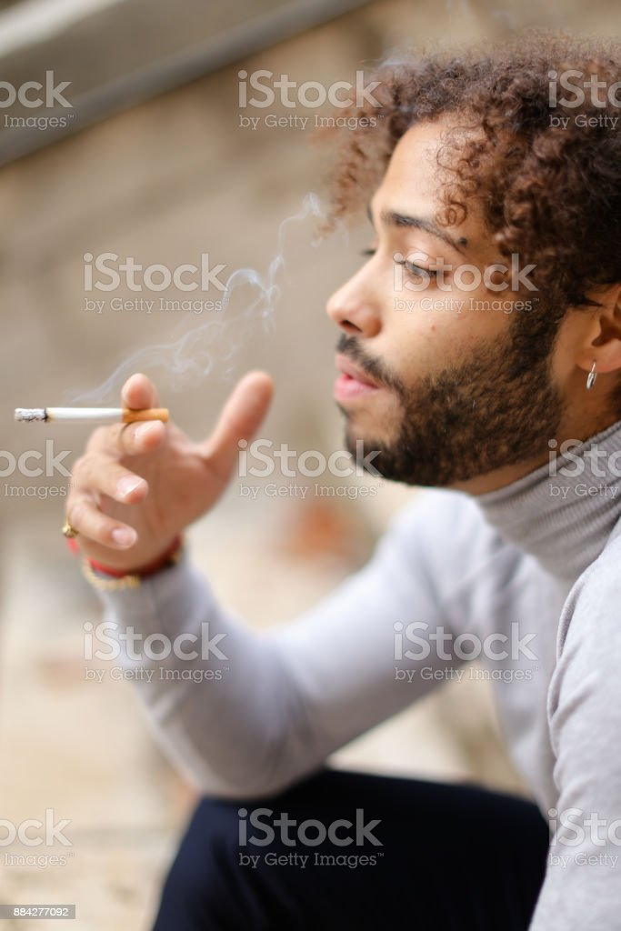 Young mulatto smoker coughing on steps with cigarette stock photo