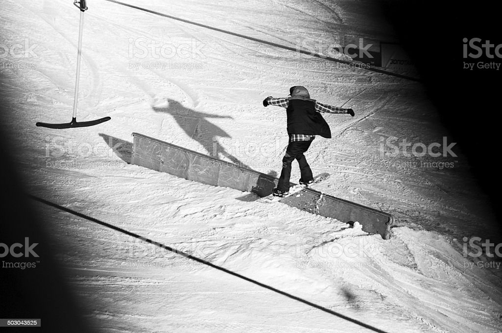 young snowboarder sliding on rail stock photo