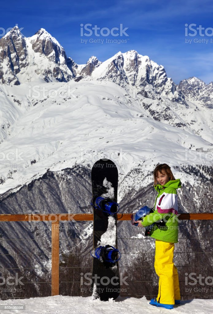 Young snowboarder with helmet in hands and snowboard on viewpoint in winter mountain at sun day stock photo