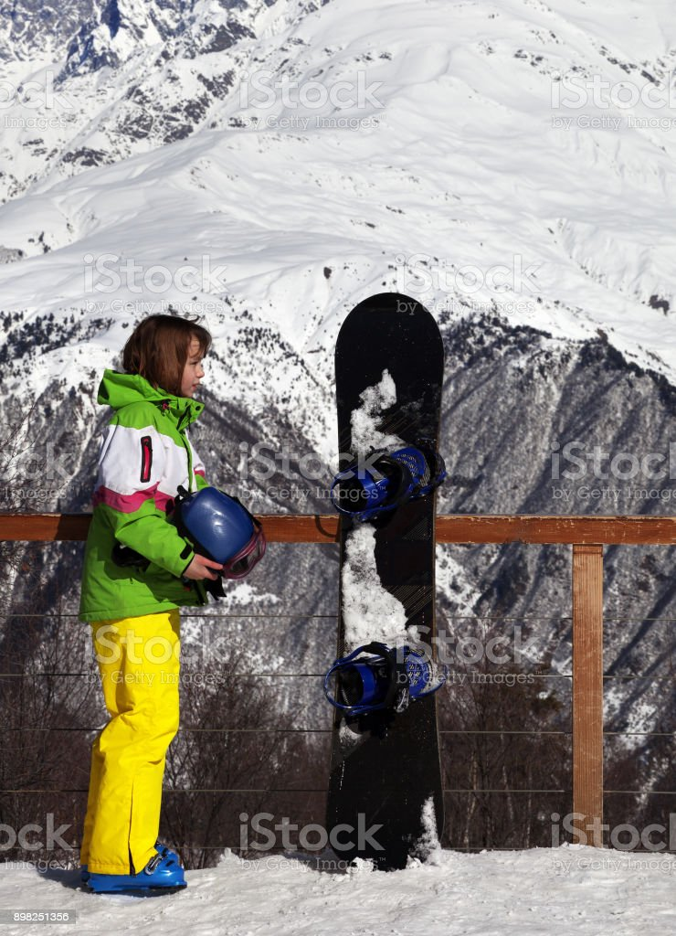Young snowboarder with helmet in hands and snowboard on viewpoint in winter mountain stock photo